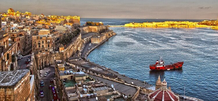 A view of the glimmering buildings and bright boats on the coast of Valletta, Malta at sundown.