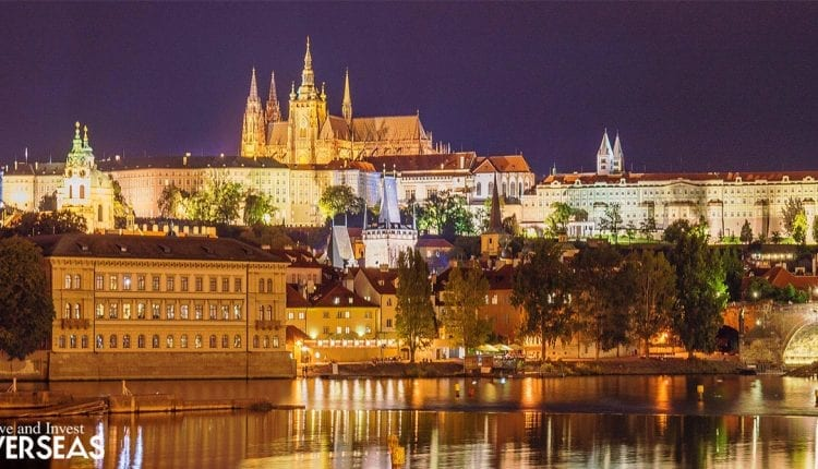 the Prague skyline by the river lit up at night