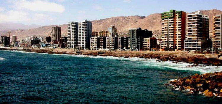 A view of Antofagasta, Chile with the water in front and mountains in the background.