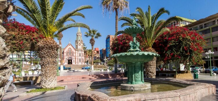 a plaza with plants and a fountain in Arica, Chile