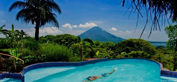 A warm, sunny day in Nicaragua with a swimming pool in the foreground and volcano in the background