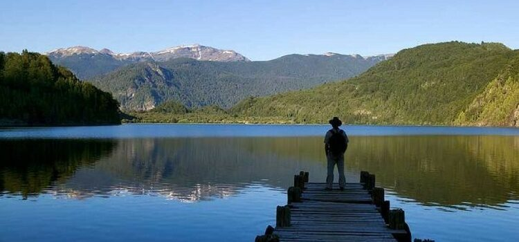 A retired man in Chile looking at a lake and mountains.