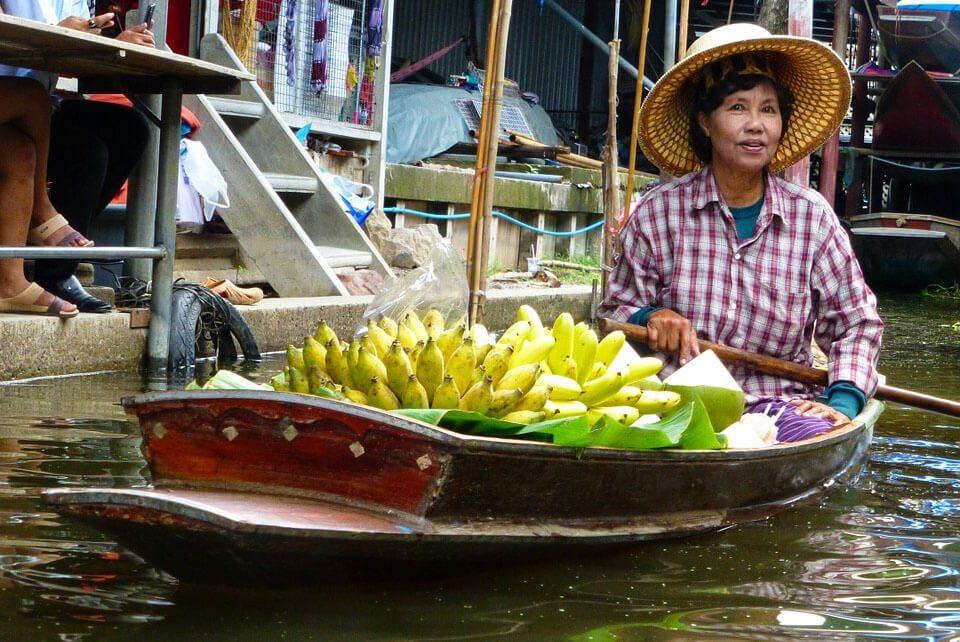 Thai woman floating on river in boat loaded with bananas