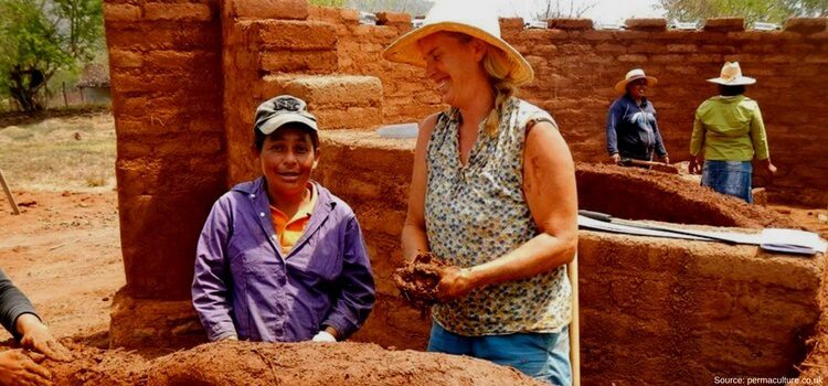 A couple of women working in Nicaragua building a wall from natural materials.