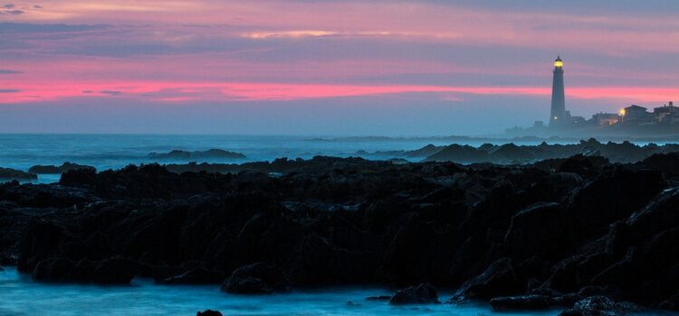 the sun going down on the shores of Uruguay with a bright pink sky over the dark blue waters and a lighthouse in the backdrop