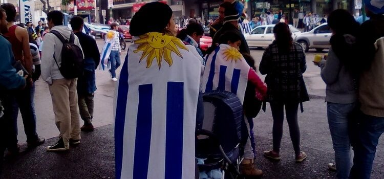 Uruguayan people in the streets with a flag over their back supporting their country.