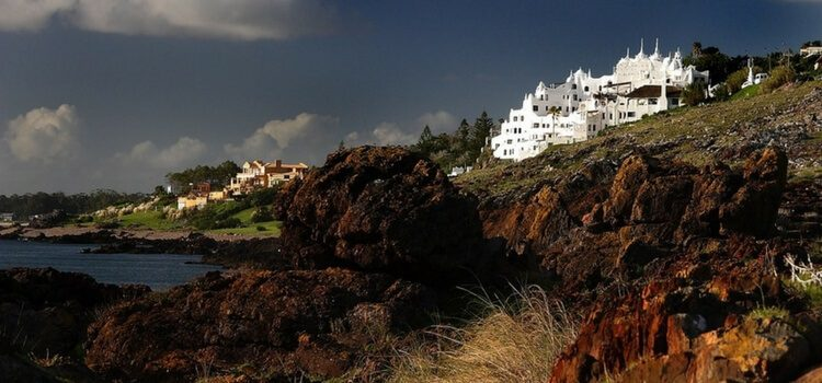A large white property in Uruguay overlooking a cliff and the ocean.