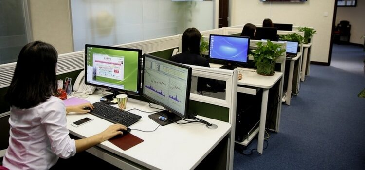 Four women sitting at their desks working in Ireland, each with computer monitors showing graphs.