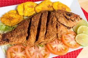 Pargo frito (fried fish) laid out on a plate with plantains, tomatoes, and limes.