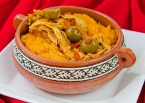 A bowl of Tamal de Olla topped with green olives.