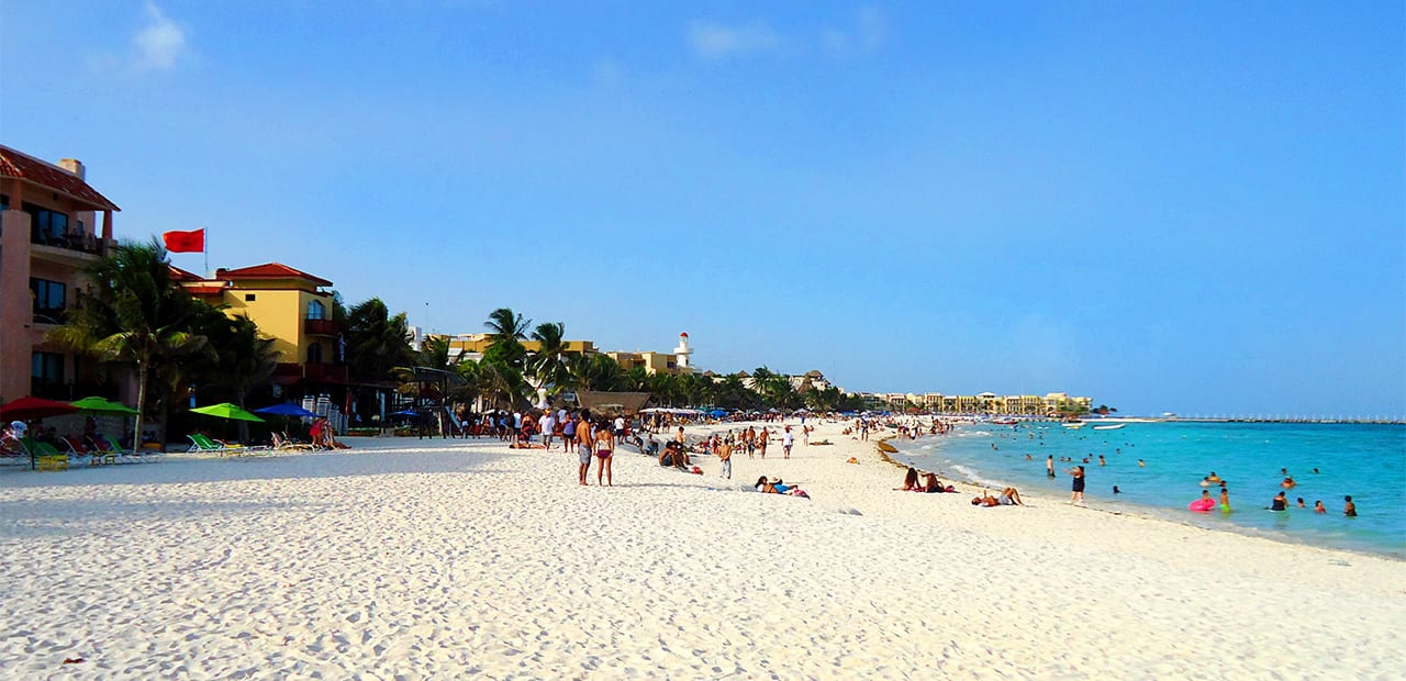people swimming and relaxinf on the beacj in playa del carmen mexico