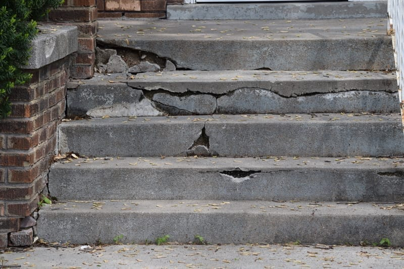 Short set of cement steps is cracked and broken and in need of repair.