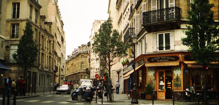 busy street corner in paris with people, cars and motorcycles