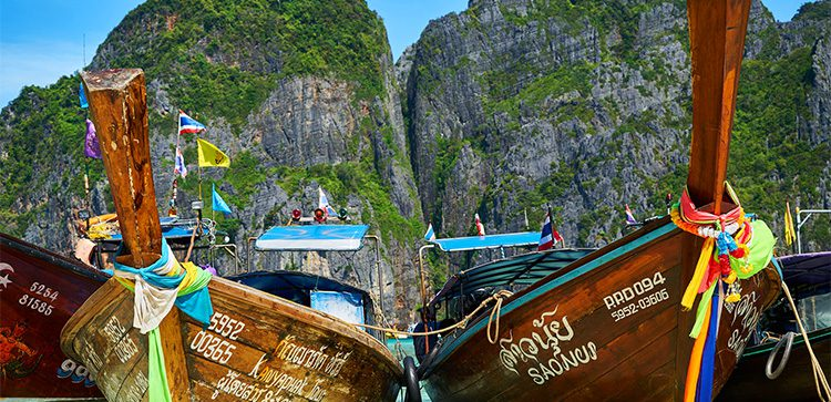 close-up of longtail boats on Thailand with cliffs in the background