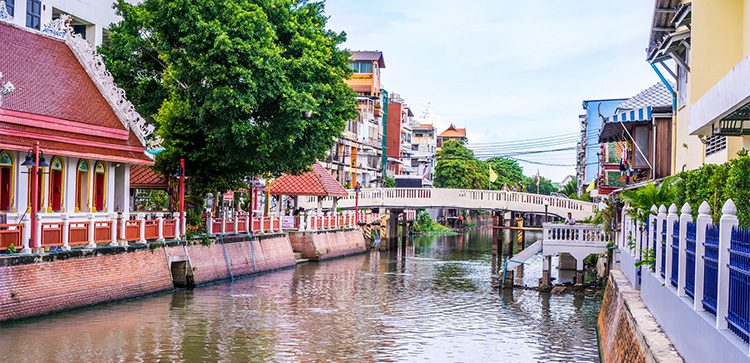 a small canal running through buildings in Thailand