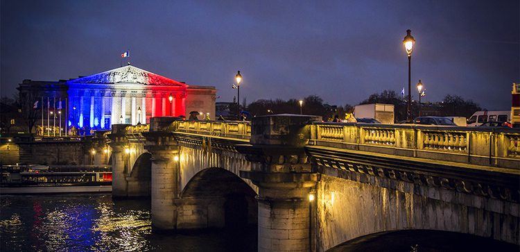 the national assembly of Paris lit up with red white and blue lights