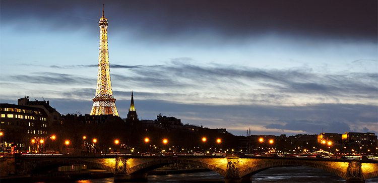 a night view of Paris with the lit up Eifel Tower and Seine River
