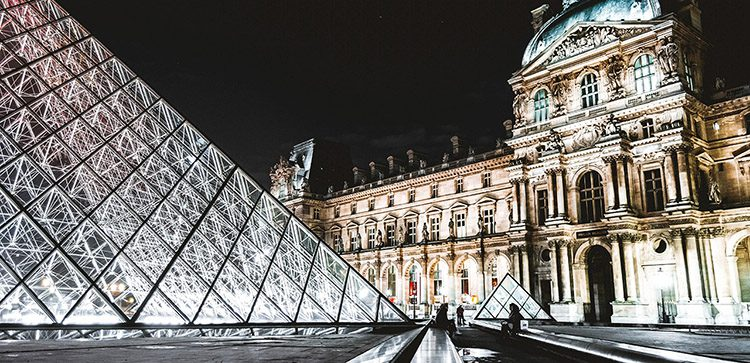 The glass pyramid of the Louvre Museum lit up at night