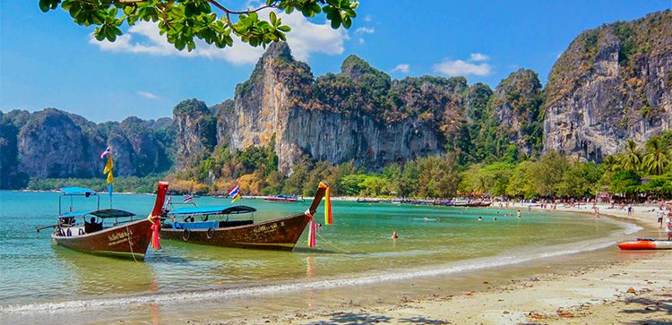 long tail boats on a beach in Thailand with cliffs in the background
