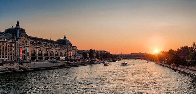 the sun setting in the distance over the Seine river