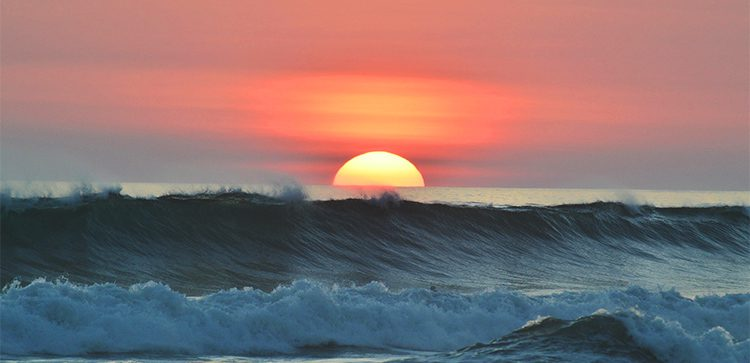 big waves rollingin with red sky and sunset in background