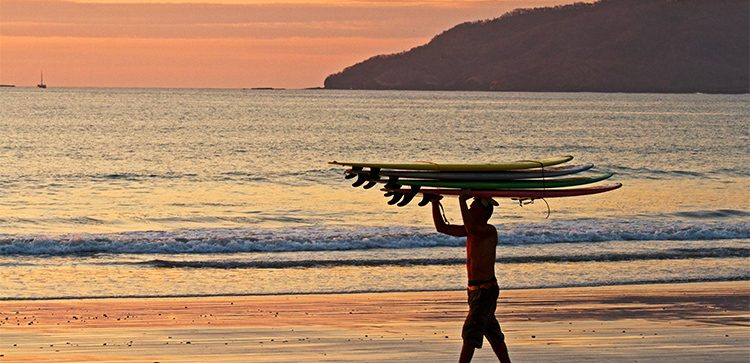 A man carrying four surfbord on his head walking on the beach at sunset