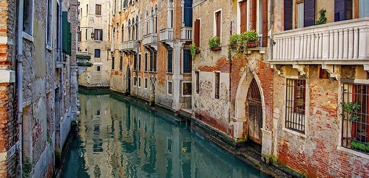 a narrow canal runs between stone buildings in Venice