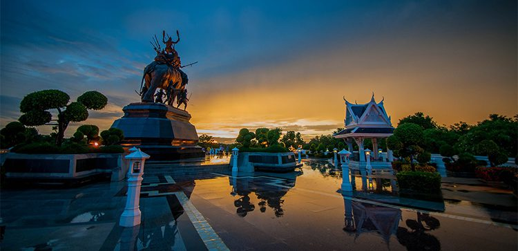 sunset view of statues and temples in Thailand with reflecting pool in foreground