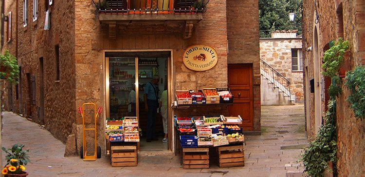 A corner store on a narrow cobblestone street in Italy