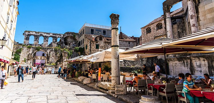 people in an outdoor plaza with cafes and ruins in croatia
