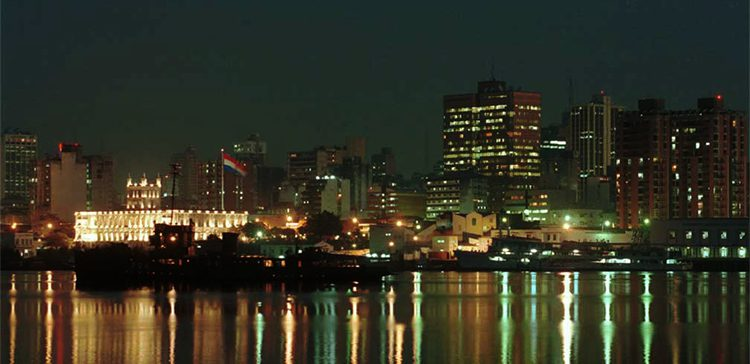 buildings at night by the water in Paraguay