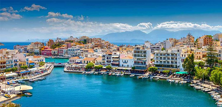 A seaside town on the island of Crete, complete with green and blue water.