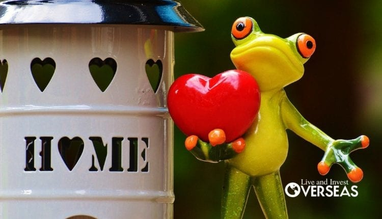 a glass statue of a frog holding a heart next to a cylinder that says home
