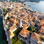 aerial view of red roofed buildings on the coast in croatia