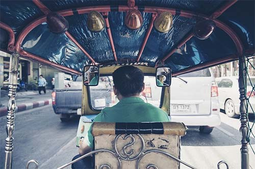 a tuk tuk driver as seen from the back seat of the tuk tuk
