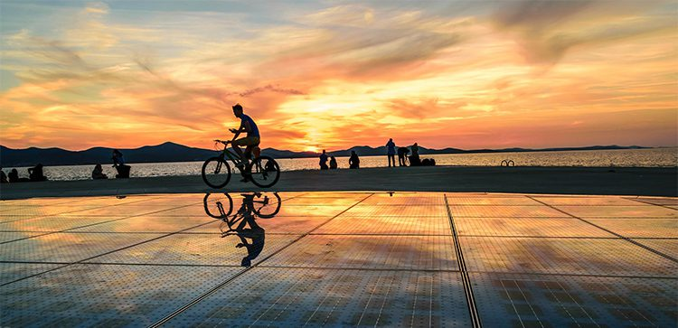 a silhouetted person on a bicycle at sunset