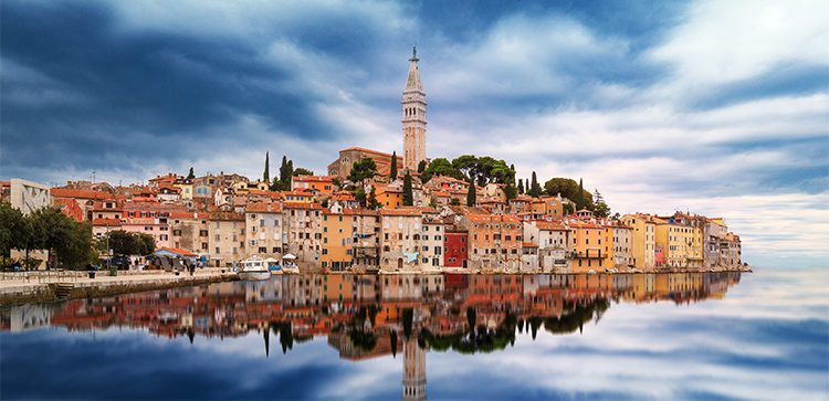 a classic croatian town by the water with dark clouds overhead
