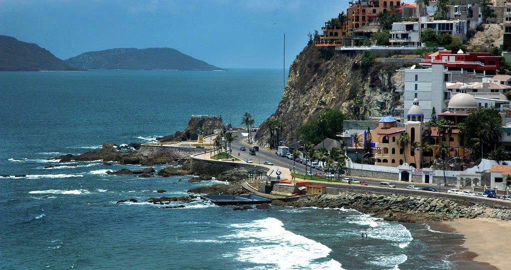 The coast of Mazatlan, Mexico with homes on the hillside and cars driving next to the waters.
