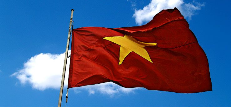 A Red Vietnam Flag With A Yellow Star in The Middle Flaps in the Wind