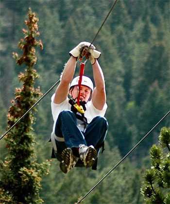a man ziplining through trees