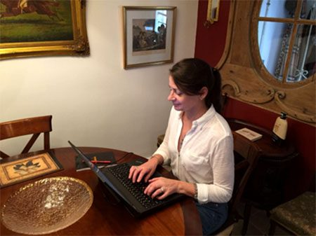 Kathleen sitting at a laptop in her paris apartment