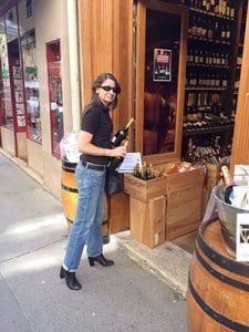 Kathleen holding a bottle of wine outside a wine shop