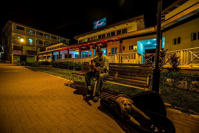 A man sitting on a bench in San Ignacio playing music