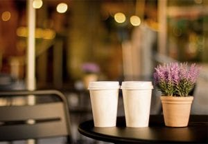 Two paper coffee cups on a table at a cafe