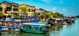 Boats lined up along the river in Hoi An, Vietnam with yellow properties along the bank.