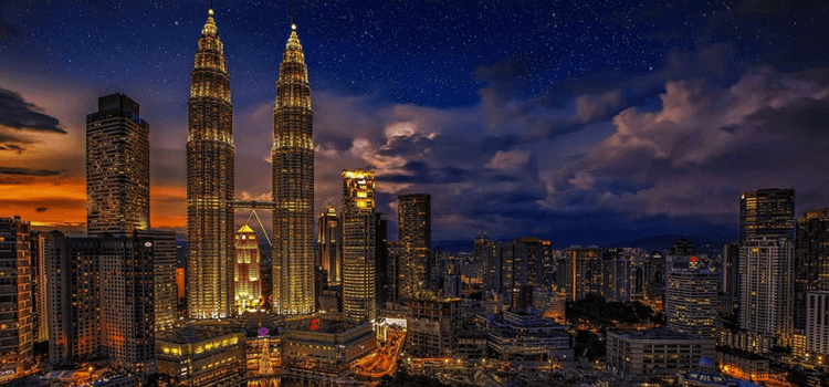 The sun going down over Kuala Lumpur, with building lit up and the Petronas Towers reaching high into the sky.