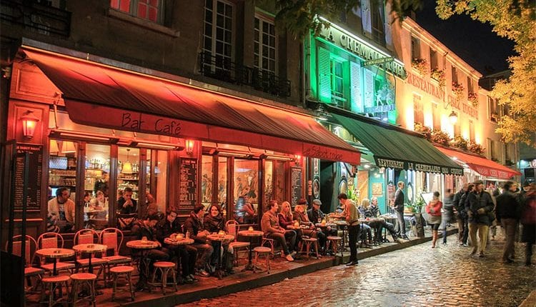 Busy cafes in montmartre lit by colorful street lights