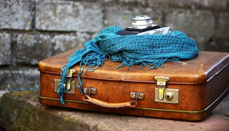 A blue scarf and camera sit atop a leather suitcase