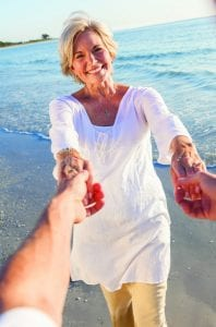 Happy senior woman holding hands with a man on the beach