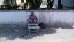 A Shoe shiner awaiting customers